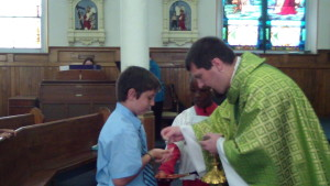 Noah receiving First Holy Communion from Fr. Naples